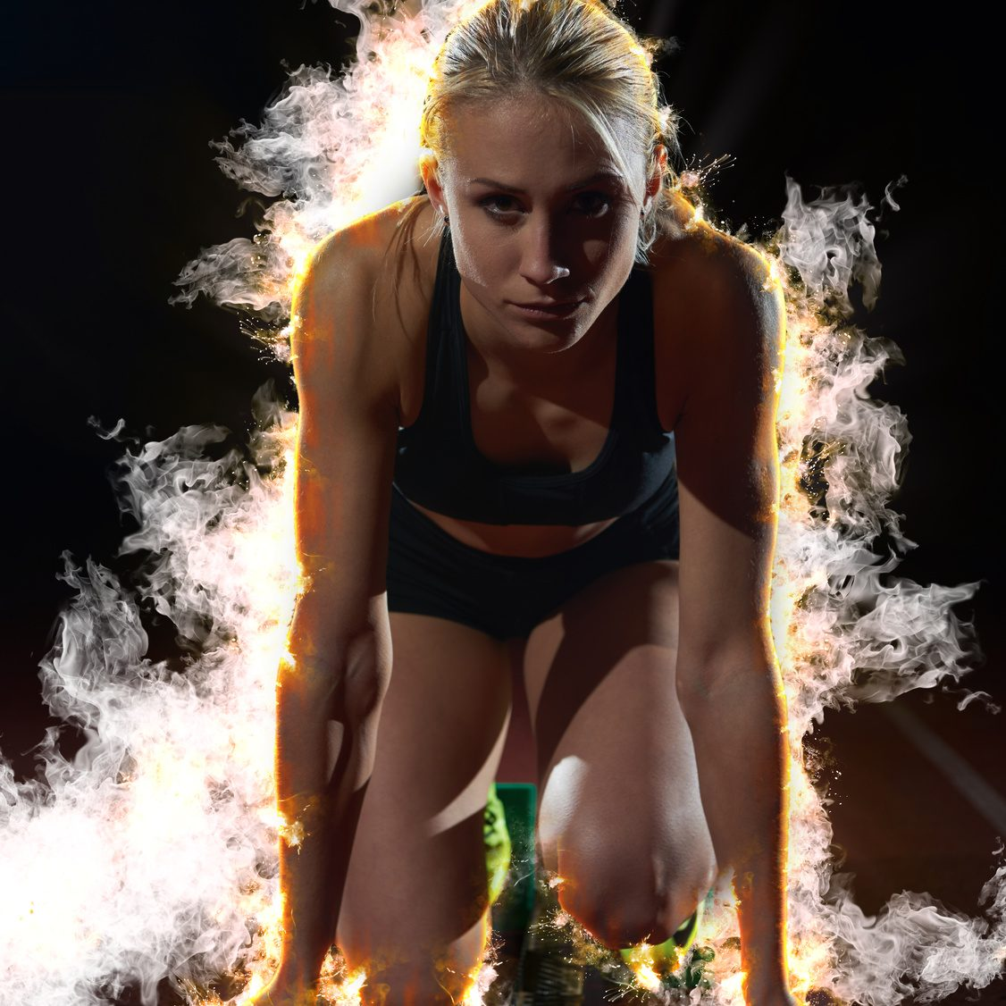 design with fire, smoke  and burm  of woman  sprinter leaving starting blocks on the athletic  track. Side view. exploding start